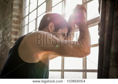 Side view of a man looking outside at the gym