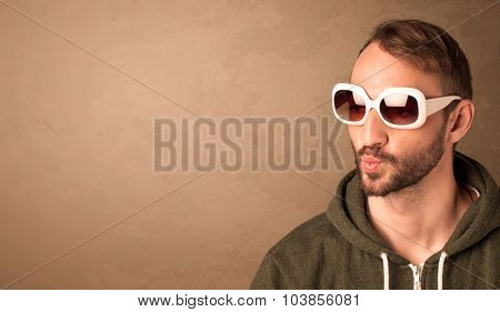 Portrait of a young pretty man with sunglasses and copyspace on brown background