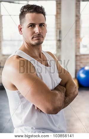 Portrait of a muscular man with arms crossed at the gym