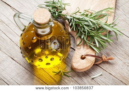 Fresh garden rosemary and olive oil on wooden table