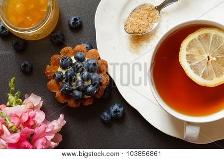 cup of tea with cake and flowers