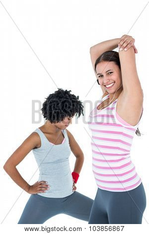 Happy fit woman exercising while female friend stretching against white background