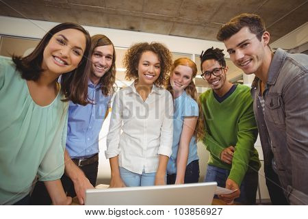 Portrait of smiling business people with laptop during meeting in office