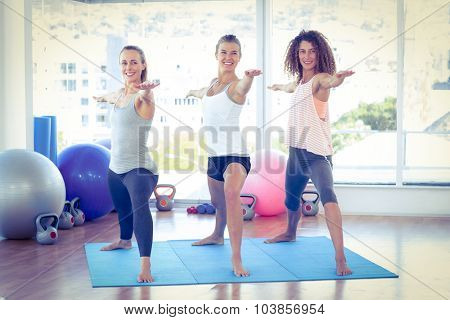 Happy woman with arms outstretched in fitness studio stretching on yoga mat