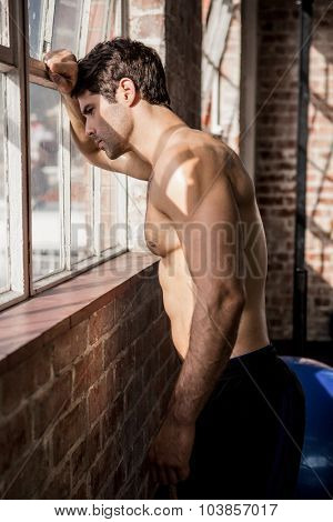 Shirtless man looking outside from window at the gym
