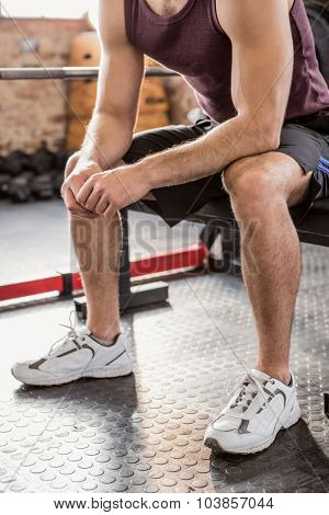 Man sitting on bench at the gym