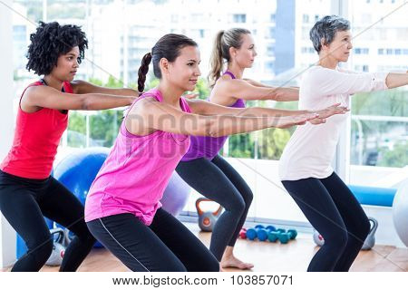 Side view of women exercising in fitness studio
