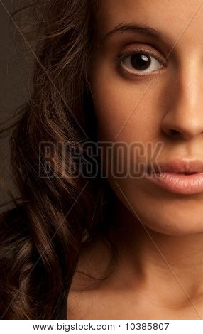 Young Woman Close-up Portrait Half Face On Dark Background