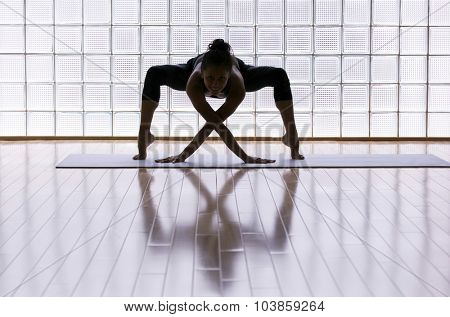 Young woman practicing in a yoga studio. Artistic shot showing reflection and lines.