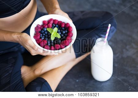 Above shot of a woman with a bowl of berries and a bottle of almond milk wearing a sportive outfit.