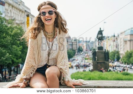 Hippy-looking Woman Tourist Sitting On Stone Parapet In Prague