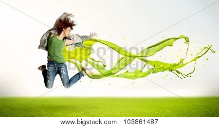 Pretty girl jumping with green abstract liquid dress concept in nature