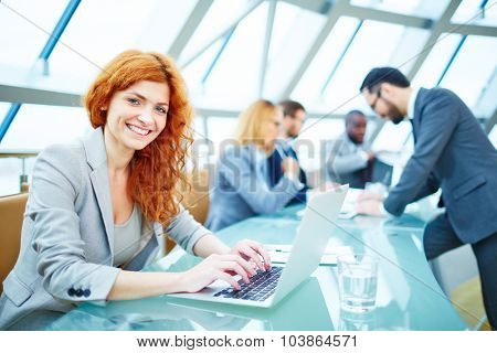 Pretty young businesswoman looking at camera while typing