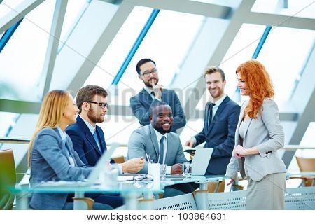 Modern employees communicating at meeting