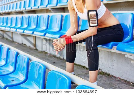 Fit girl in activewear sitting at stadium and listening to music
