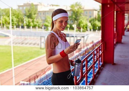 Happy girl with smartphone and earphones reading sms at stadium