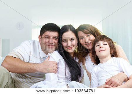 Happy family of four looking at camera