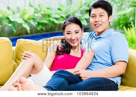 Chinese woman and man of sofa in their home