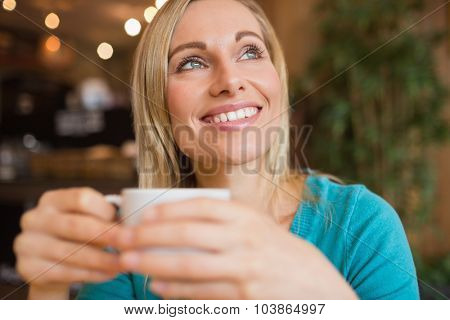 Close-up thoughtful young woman holding coffee cup in restaurant