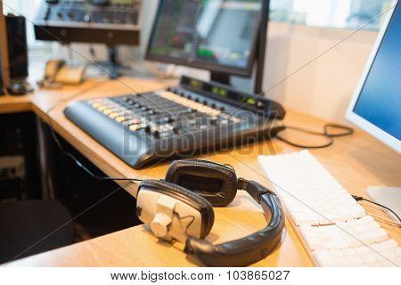 Close-up of headphones on desk in radio studio