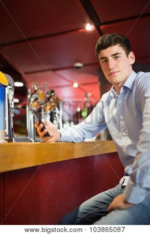 Portrait of confident man holding mobile phone while sitting at bar counter
