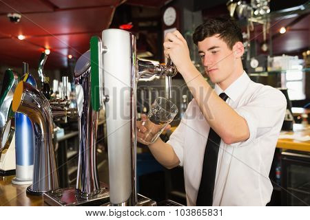 Confident bartender holding glass standing in front of beer dispenser