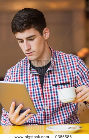 Young man using digital tablet while holding coffee cup at cafe