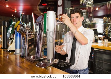 Portrait of confident bartender holding glass standing in front of beer dispenser