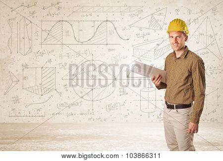 Handsome engineer calculating with hand drawn background concept