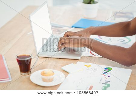High angle view of cropped hands working on laptop at desk in office
