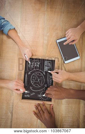 Overhead view of cropped hands writing business terms on slate with person using digital tablet at table