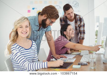 Portrait of smiling woman using digital tablet with coworkers working at computer desk