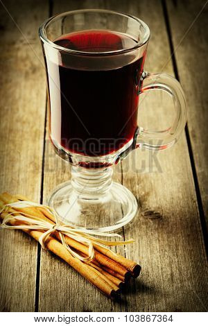 Glass of red mulled wine on wooden table