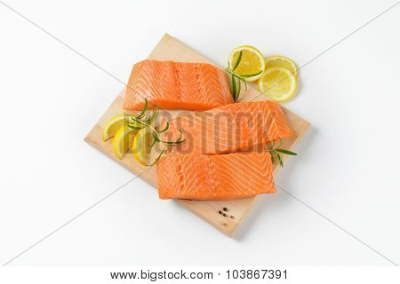 three raw salmon fillets on wooden cutting board