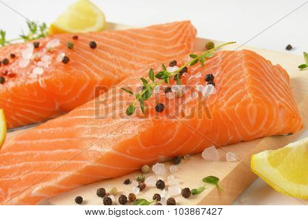 close up of two raw salmon fillets with spice on wooden cutting board