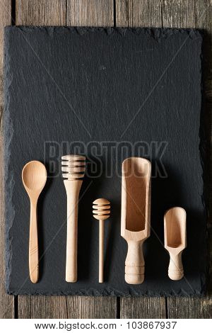 Wooden kitchen utensils on slate