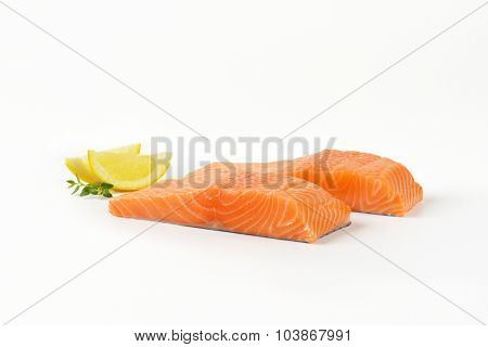 two raw salmon fillets on white background