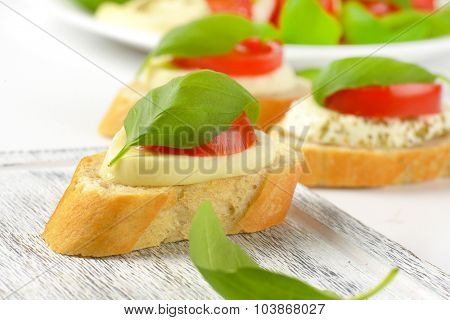 detail of mozzarella sandwiches on wooden cutting board