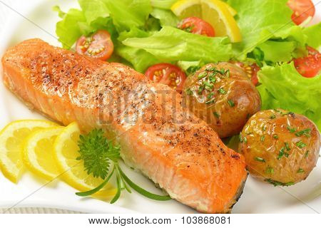 detail of pan fried salmon fillet served with roasted potatoes and fresh vegetables