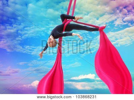 Child Hangs Upside Down On Aerial Silks In Rainbow Sky