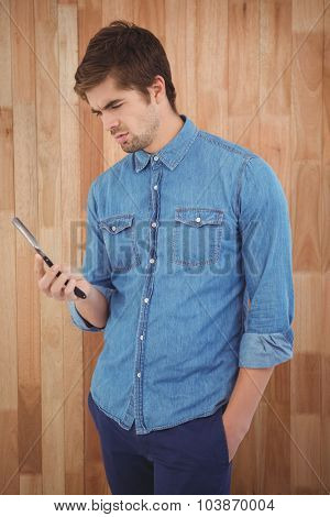 Hipster holding straight edge razor while standing against wooden wall