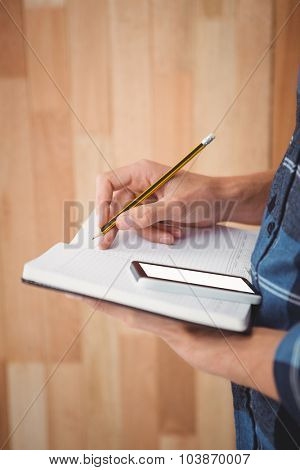 Cropped image of man writing on diary with pencil against wooden wall