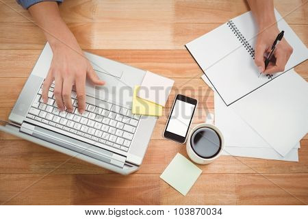 Cropped hand of creative businessman writing on spiral book while using laptop at desk in office