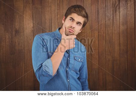 Thoughtful man with hand on chin standing against wooden wall