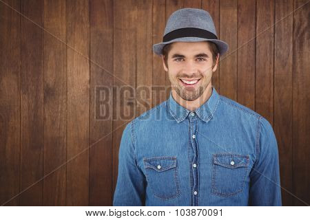 Portrait of happy hipster wearing hat against wooden wall
