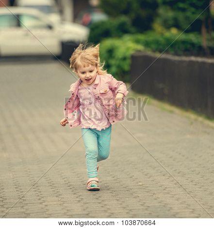 little cute girl running the street