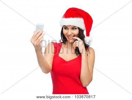 people, holidays, christmas and technology concept - beautiful sexy woman in red santa hat taking selfie picture by smartphone