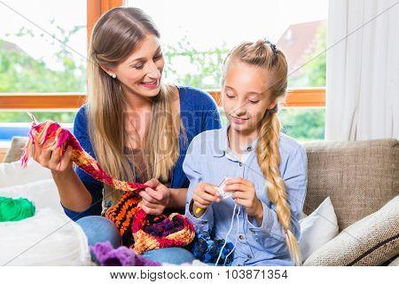 Mother teaching daughter knitting