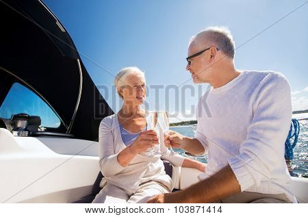 sailing, age, travel, holidays and people concept - happy senior couple clinking champagne glasses on sail boat or yacht deck floating in sea