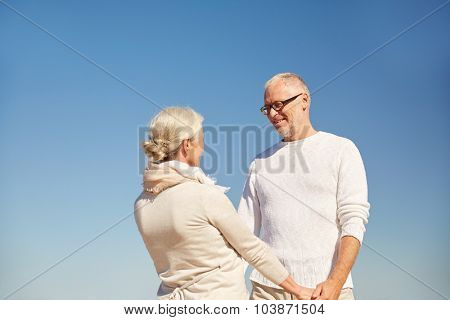 family, age and people concept - happy senior couple holding hands talking outdoors